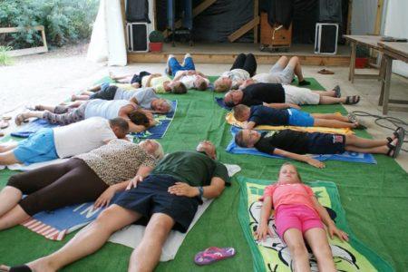 groupe de personnes allongées sur des serviettes, en cercle, et qui font de la relaxation